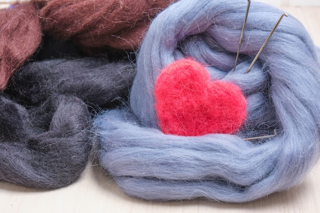 Coração feltro de lã de uma agulha e um novelo de lã na mesa close up