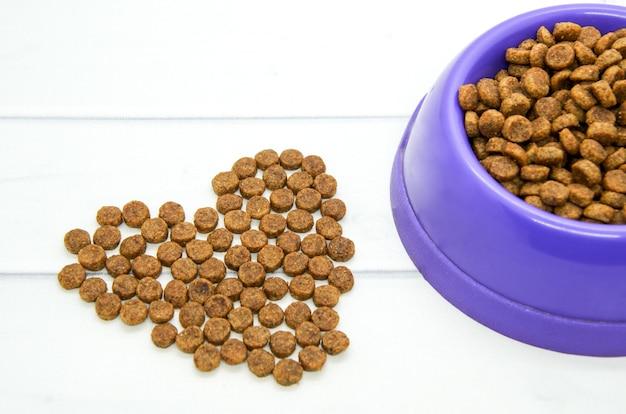 Coração forrado com comida de animal seca e tigela de plástico cheia de comida.