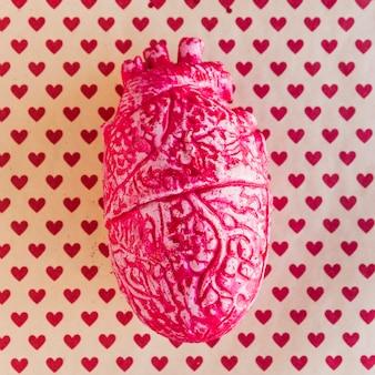Coração humano de cerâmica vermelha na mesa com padrão de coração
