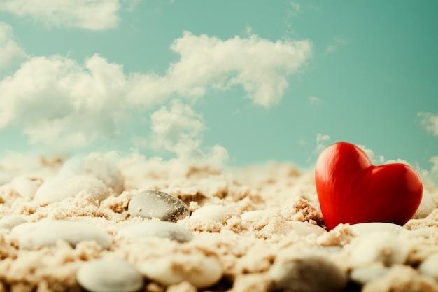 Coração na areia à beira-mar