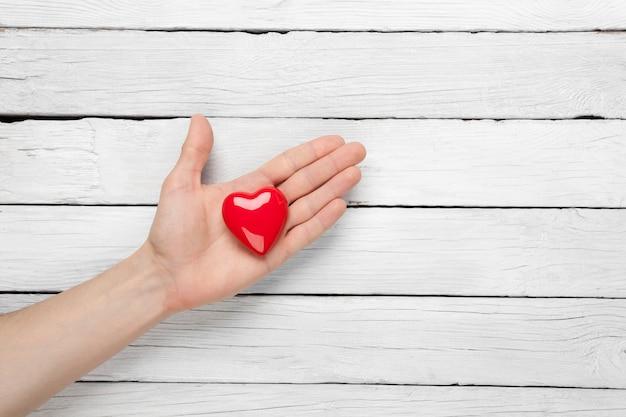 Coração na mão do homem em uma madeira