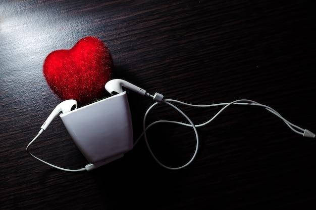 Coração na panela com fone de ouvido branco e mesa de madeira