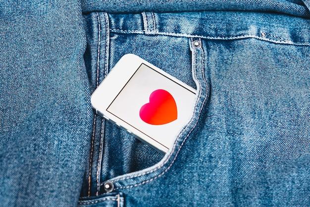 Coração na tela de um celular, sentado no bolso da calça jeans