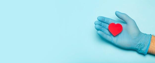Coração nas mãos de um médico em uma bandeira colorida fundo doação caridade tratamento de saúde ajudar ...
