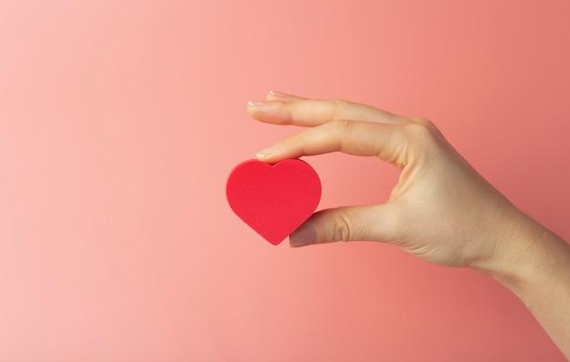Coração nas mãos de uma mulher em um fundo colorido. plano de fundo para o dia dos namorados (14 de fevereiro) e o amor.