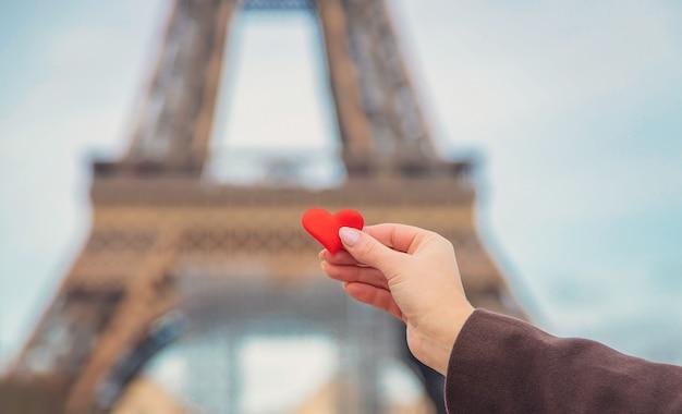 Coração nas mãos perto da torre eiffel em paris. foco seletivo.