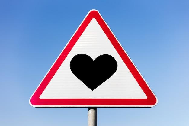 Coração negro no sinal de estrada no céu azul.