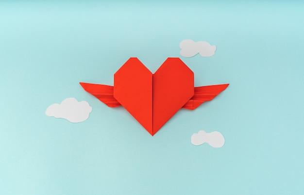Coração origami de papel vermelho com asas e nuvem no fundo azul