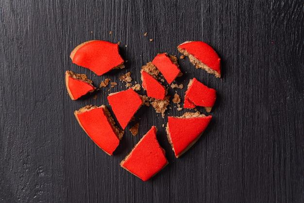 Coração partido em uma mesa de madeira preta