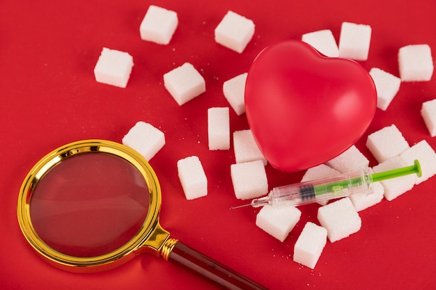 Coração partido feito de cubos de açúcar e uma seringa em um fundo vermelho. conceito de diabetes. vista de cima. crie espaço.