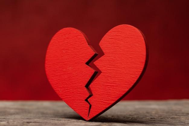 Coração partido. rachadura no coração vermelho, rompendo o relacionamento. fundo vermelho.