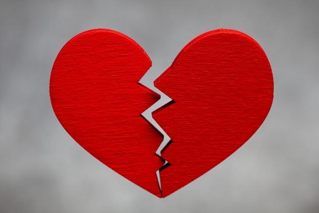 Coração partido. rachadura no coração vermelho, rompendo o relacionamento. plano de fundo cinza.