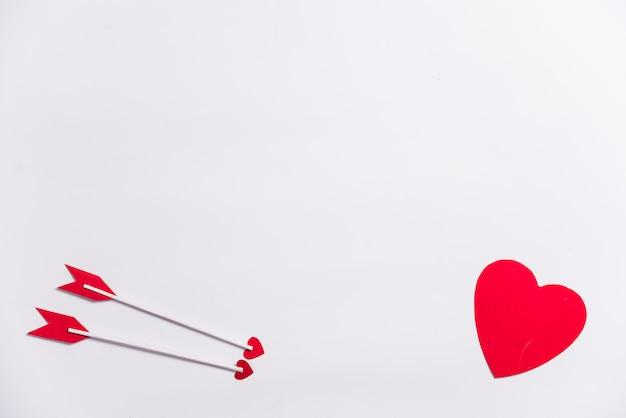 Coração pequeno com duas flechas de amor