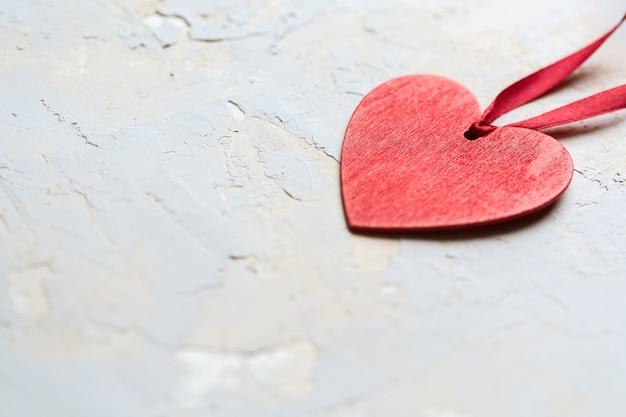 Coração pintado de vermelho com fita em plano de fundo texturizado cinza, cartão minimalista do dia de são valentim