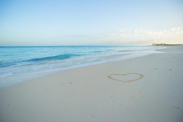 Coração pintado em areia branca em uma praia tropical