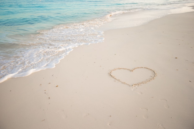 Coração pintado na areia branca em uma praia tropical