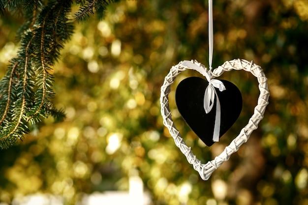 Coração preto colocado no coração branco pendurado na árvore