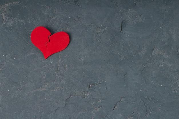 Coração quebrado na parede do cimento do grunge - ame o conceito. copie o espaço