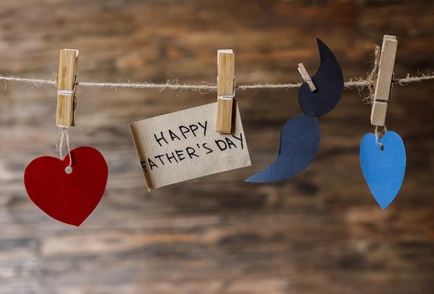 Coração retrô artesanal pendurado sobre madeira com a inscrição do dia do pai feliz