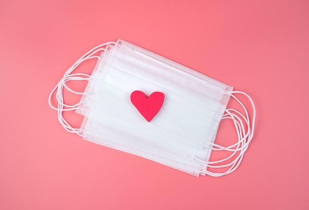 Coração rosa em máscaras médicas brancas. vista de cima, com espaço para copiar. conceito 14 de fevereiro.