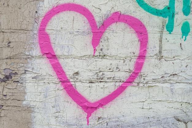 Coração rosa no fundo da parede de tijolo.