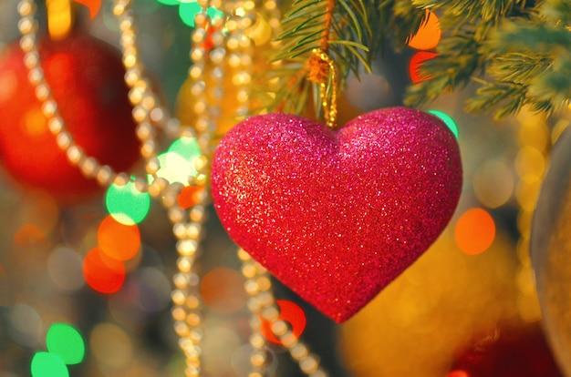 Coração rosa pendurado no galho de árvore de natal