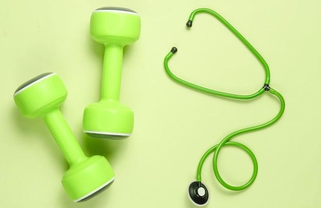 Coração saudável e músculos fortes. halteres e estetoscópio sobre fundo verde. vista do topo. postura plana