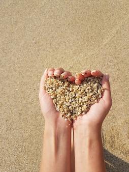 Coração suave moldando as mãos femininas acima do mar e da praia.