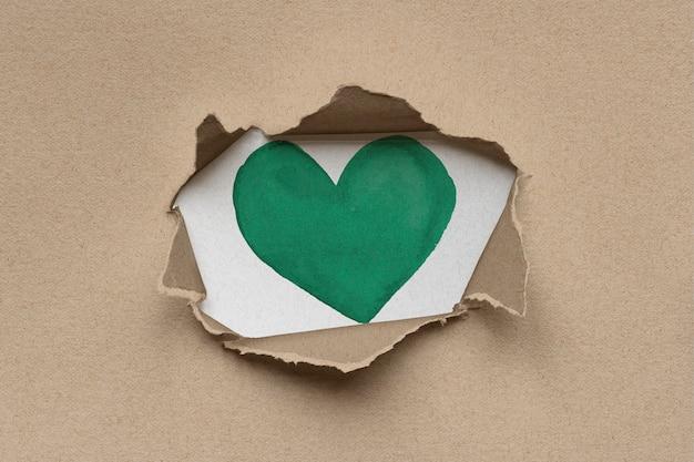 Coração verde dentro de papelão kraft marrom rasgado e ecológico