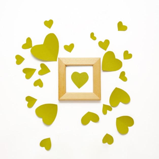 Coração verde em moldura de madeira. vista superior do dia dos namorados decorações plana leigos. corações,