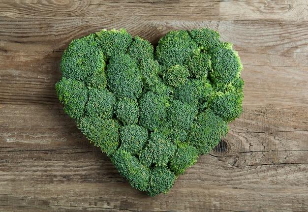 Coração verde forrado com brócolis em um de madeira