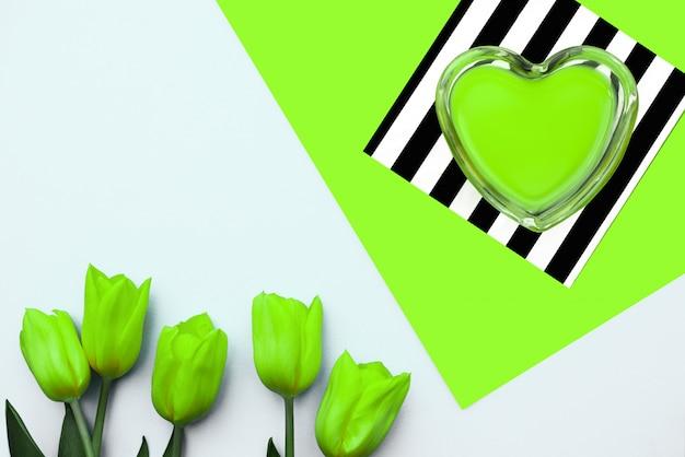 Coração verde neon e tulipas amarelas sobre fundo verde listras