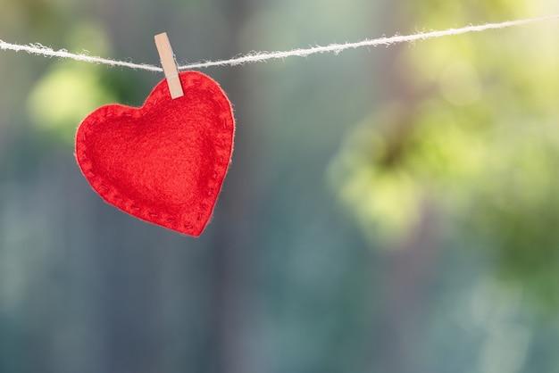 Coração vermelho anexado com um prendedor de roupa no fundo desfocado. conceito de dia dos namorados com espaço de cópia para texto publicitário