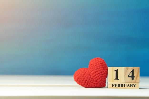Coração vermelho ao lado do calendário de bloco de madeira