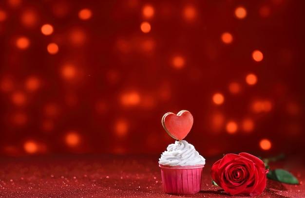 Coração vermelho brilhante na parte superior do muffin para o dia dos namorados com flor rosa como uma doce declaração de amor. copie o espaço
