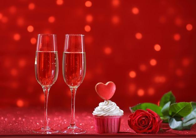 Coração vermelho brilhante no bolinho para o dia dos namorados com flor rosa e duas taças de champanhe. copie o espaço
