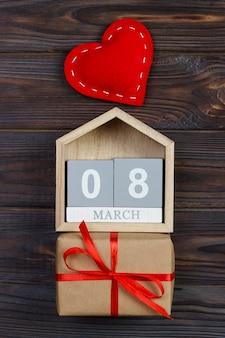 Coração vermelho brilhante no calendário do bloco de madeira com caixa de presente, 8 de março, comemorando o dia internacional da mulher