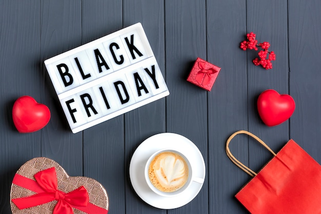 Coração vermelho, café quente cappuccino, saco de papel vermelho, caixa de presente, caixa de luz com texto sexta-feira negra