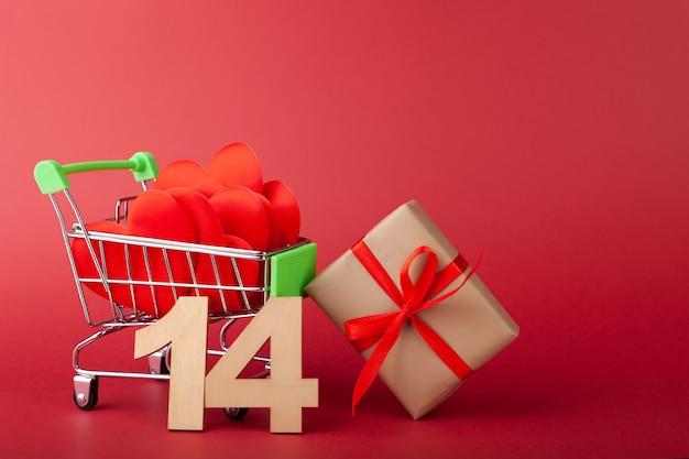 Coração vermelho, caixa de presente com fita vermelha dentro do mini carrinho de supermercado com fundo colorido