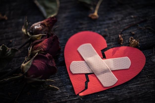 Coração vermelho com a rosa secada do vermelho no fundo de madeira. coração quebrado conceito