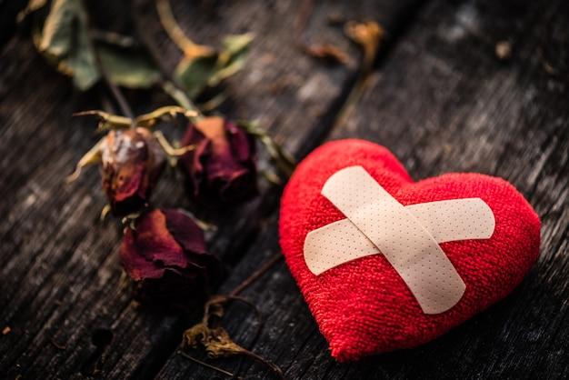 Coração vermelho com a rosa secada do vermelho no fundo de madeira. coração quebrado