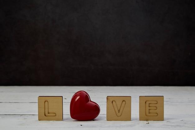 Coração vermelho com bloco de madeira vazio em madeira branca