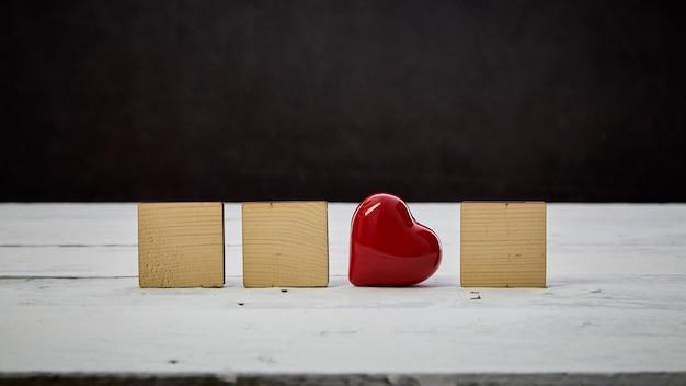 Coração vermelho com bloco de madeira vazio na mesa de madeira branca