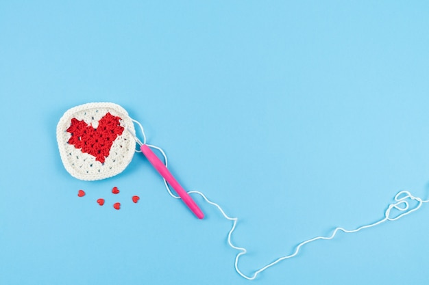 Coração vermelho com borda branca de crochê sobre fundo azul.