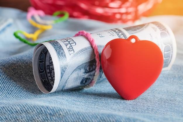 Coração vermelho com cem dólares, deitado sobre jeans azul velho.