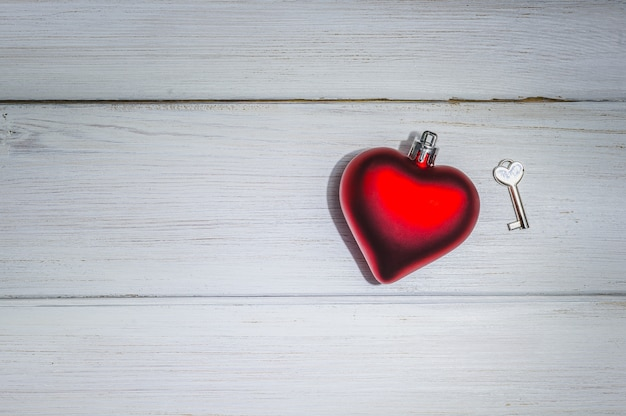 Coração vermelho com chave no fundo de madeira branco