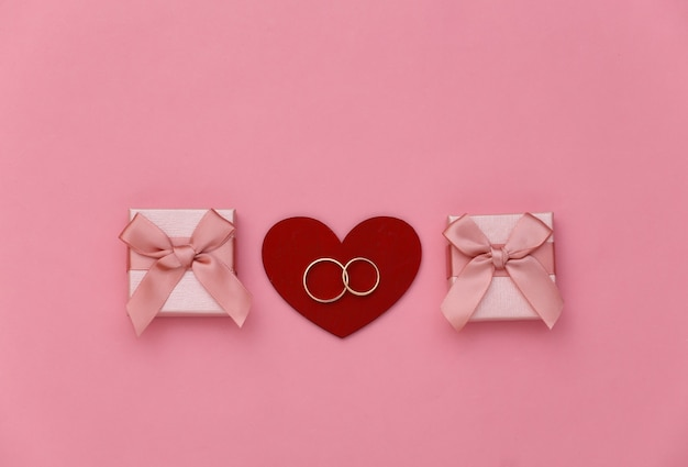 Coração vermelho com dois anéis de ouro e caixas de presente em fundo rosa.