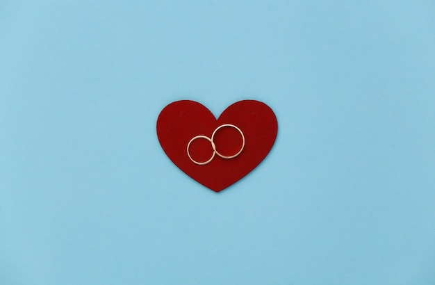 Coração vermelho com dois anéis de ouro sobre fundo azul.