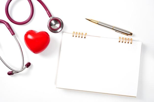 Coração vermelho com estetoscópio e caderno em fundo branco foco seletivo saúde e medicina