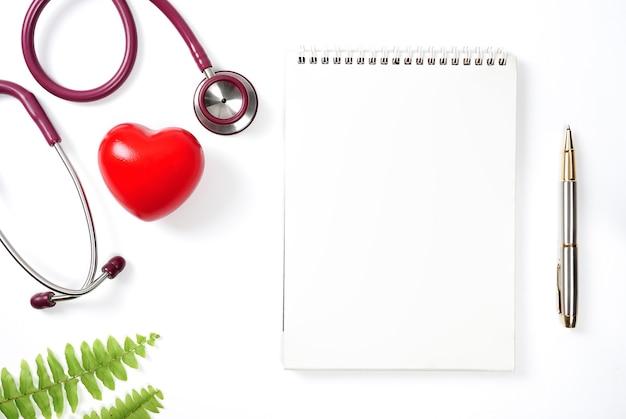 Coração vermelho com estetoscópio e caderno em fundo branco. foco seletivo